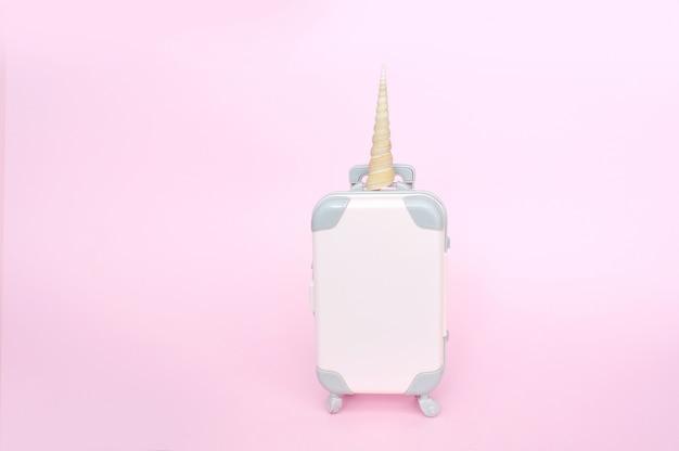 Pequeño equipaje rosado de la maleta del unicornio aislado en el fondo rosado w