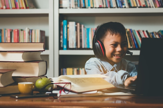 Pequeño estudiante extranjero encantador que aprende, usando la computadora con diversión y feliz.