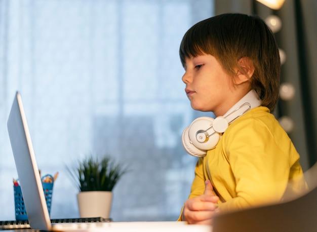 Pequeño estudiante en línea con auriculares