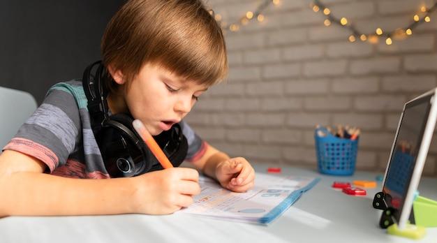 Pequeño estudiante en línea escribiendo y concentrado