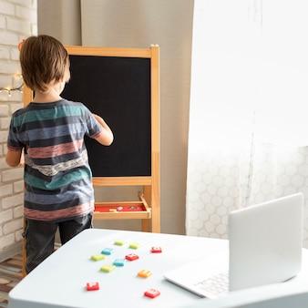 Pequeño estudiante en línea escribiendo en un tablero