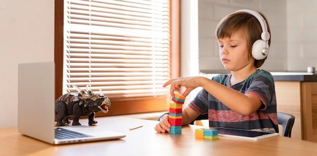 Pequeño estudiante en línea jugando con juguetes