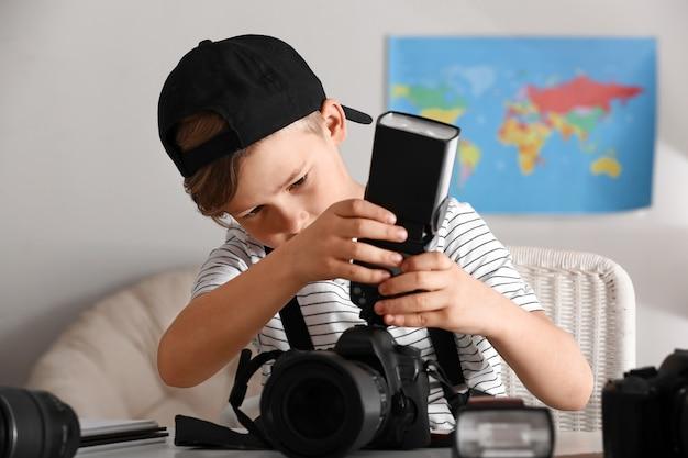 Pequeño fotógrafo lindo con cámara profesional en casa