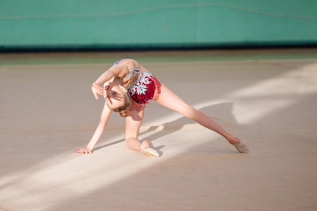 Pequeño gimnasta entrenando en la alfombra y listo para competiciones.