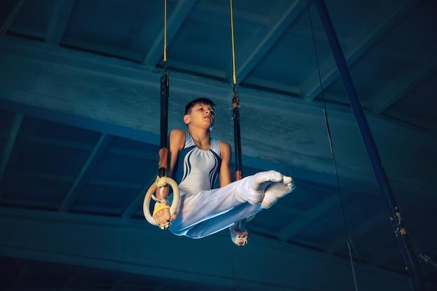 Pequeño gimnasta masculino entrenando en gimnasio, flexible y activo. chico caucásico en forma, atleta en ropa deportiva blanca practicando ejercicios de equilibrio en los anillos. movimiento, acción, movimiento, concepto dinámico.
