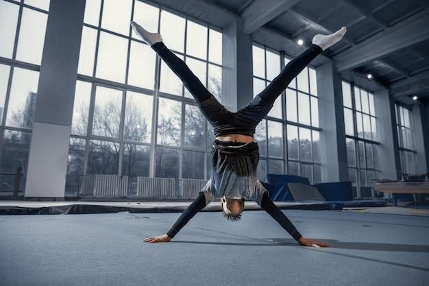 Pequeño gimnasta masculino entrenando en gimnasio, flexible y activo. niño pequeño caucásico, atleta en ropa deportiva practicando ejercicios de fuerza, equilibrio. movimiento, acción, movimiento, concepto dinámico.