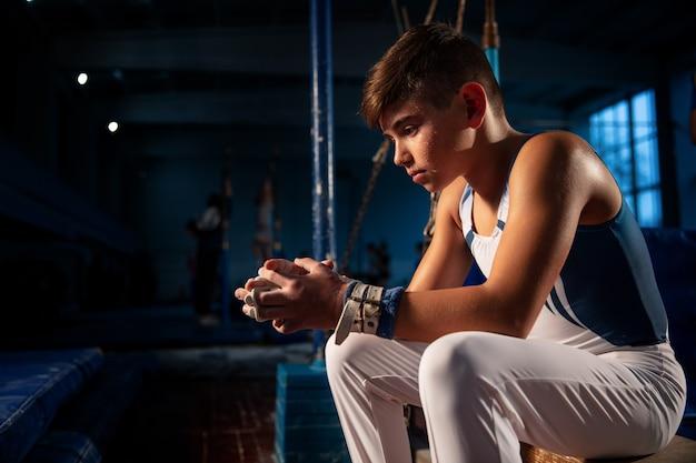 Pequeño gimnasta masculino entrenando en gimnasio flexible y activo