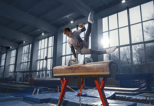 Pequeño gimnasta masculino entrenando en gimnasio, flexible y activo