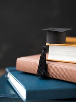 Pequeño gorro de graduación en la pila de libros