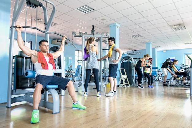 Pequeño grupo de amigos deportivos en el gimnasio, centro de fitness club