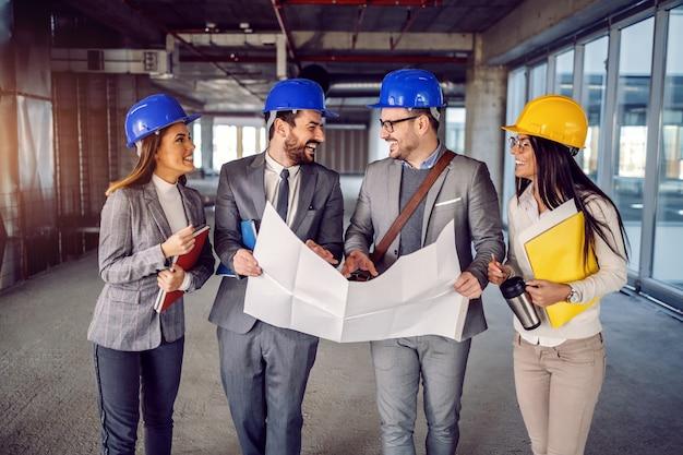 Un pequeño grupo de arquitectos dedicados y altamente motivados que caminan por el edificio que desean renovar y hablan sobre nuevas ideas para corregir los planos.