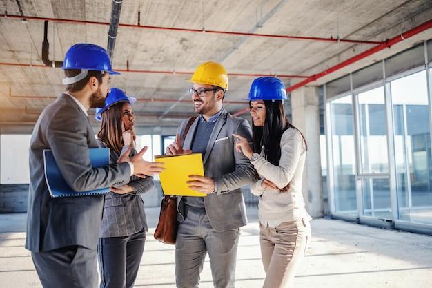 Un pequeño grupo de arquitectos jóvenes trabajadores y altamente motivados de pie dentro del edificio en proceso de construcción y hablando sobre nuevas ideas sobre el objeto relacionado con ese edificio.