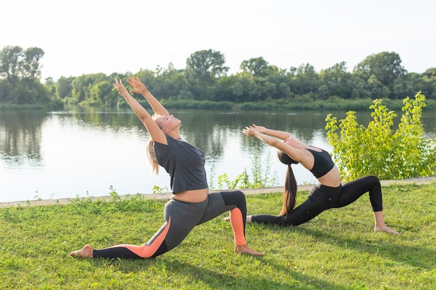 Pequeño grupo de fitness femenino haciendo yoga en el parque en un día soleado