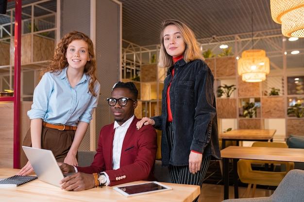 Pequeño grupo de jóvenes empleados interculturales exitosos que lo miran mientras trabajan en un nuevo proyecto comercial en la reunión