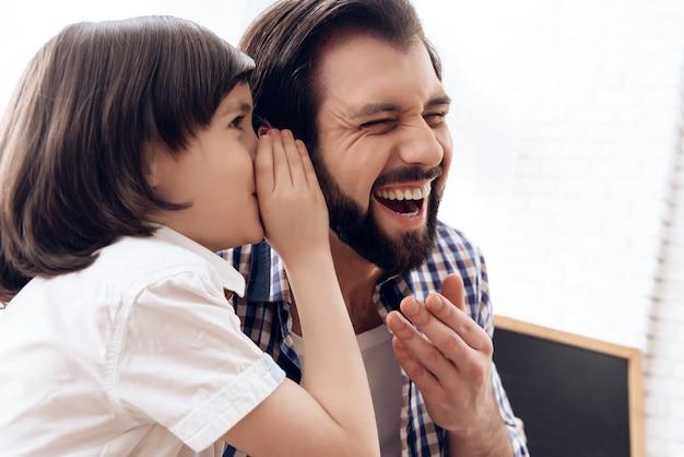 El pequeño hijo le contó a papá una broma, papá se ríe.
