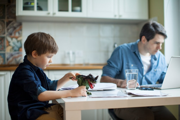 Pequeño hijo inquietante padre de trabajo independiente