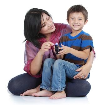 Pequeño hijo joven que abraza a su madre bastante joven en aislado sobre blanco