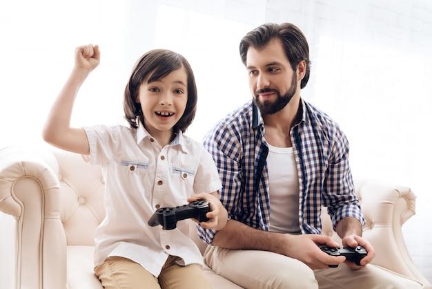 El pequeño hijo con joystick se regocija en la victoria en el juego con el padre.