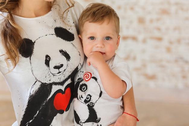 Pequeño hijo en manos de la madre. familylook de camisetas con pandas.