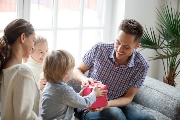 Pequeño hijo presentando un regalo para papá, familia celebrando el día del padre.