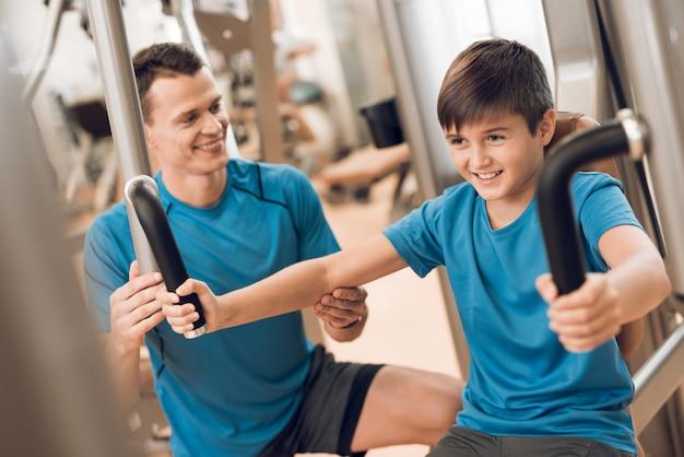 Pequeño hijo realiza un ejercicio que papá ayuda.