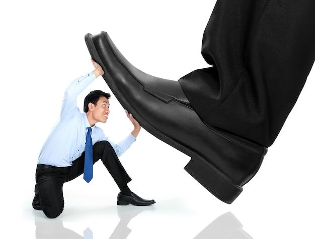 Pequeño hombre de negocios siendo aplastado por los pies