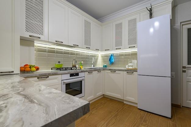 Pequeño interior de cocina clásica contemporánea blanca acogedora y cómoda con muebles de madera