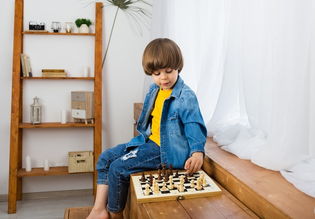 Pequeño jugador de ajedrez con cabello castaño y ropa de mezclilla está jugando al ajedrez en una habitación. desarrollo infantil temprano