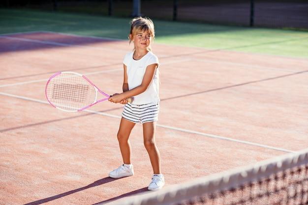 Pequeño jugador de tenis femenino en la práctica uniforme del deporte blanco en golpear con la raqueta de tenis en el entrenamiento en la cancha al aire libre en el fondo del atardecer.