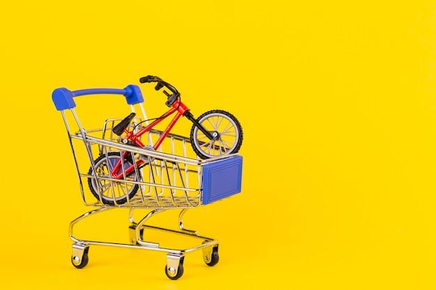 Pequeño juguete de bicicleta en el carrito de compras sobre fondo amarillo.