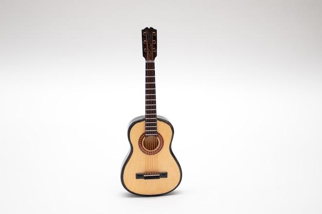 Pequeño juguete de guitarra acústica en miniatura sobre fondo blanco.