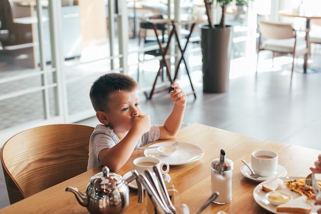 Pequeño y lindo niño desayunando en la cafetería.