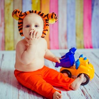Pequeño lindo sonriente bebé en tigre body-suit sentado en el suelo