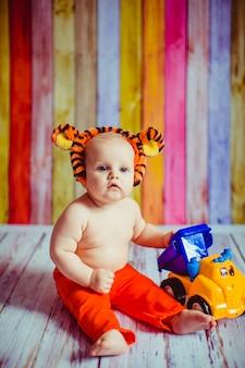 Pequeño lindo sonriente bebé en traje de tigre sentado en el suelo