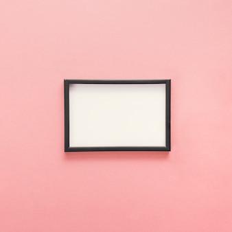 Pequeño marco en blanco sobre mesa rosa