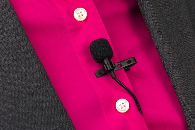 Pequeño micrófono de audio para grabación de voz con pinza para ropa sujeta a una camisa de mujer.