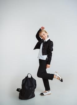 Pequeño modelo caucásico femenino posando en uniforme escolar con mochila sobre fondo blanco.