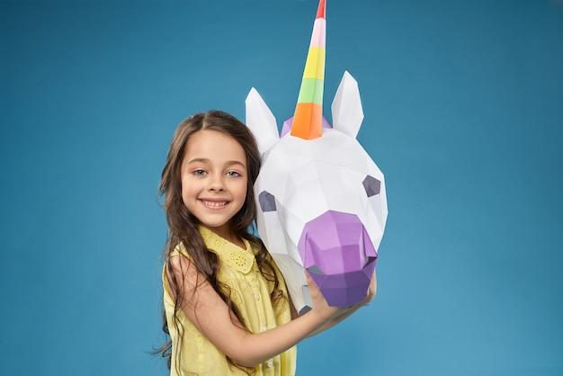 Pequeño modelo posando con unicorm 3d blanco.