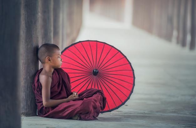 Pequeño monje de myanmar sentado en el monasterio, bagan, myanmar
