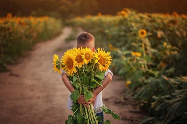 Pequeño muchacho adorable del niño que sostiene el ramo de girasoles en día de verano.