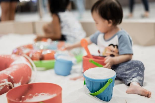 Pequeño muchacho asiático feliz con el juguete colorido en la playa de la arena, estación de verano.