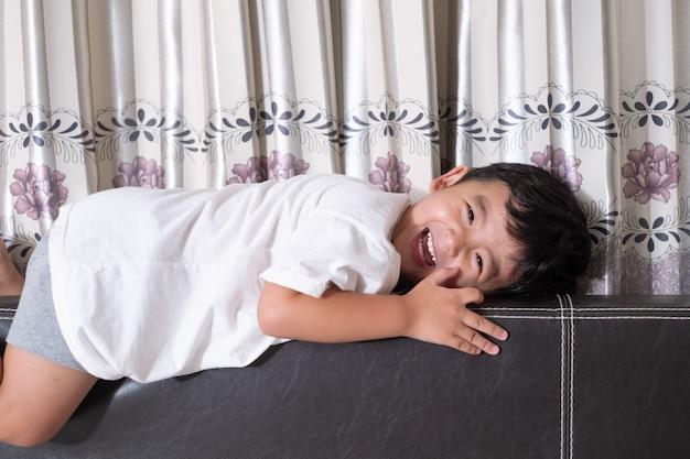 Pequeño muchacho asiático lindo de 3 años en casa en la cama, niño que miente jugando y sonriendo en la cama blanca