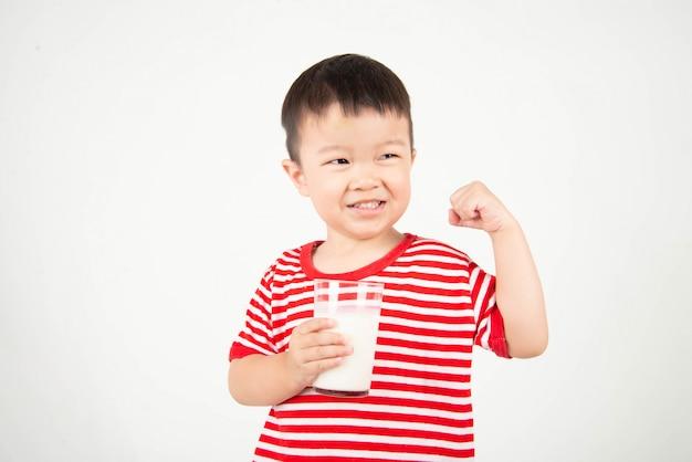 Pequeño muchacho asiático que bebe la leche del vidrio con la cara feliz