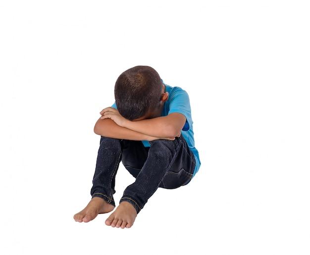 Pequeño muchacho asiático triste que se sienta en el piso aislado en blanco