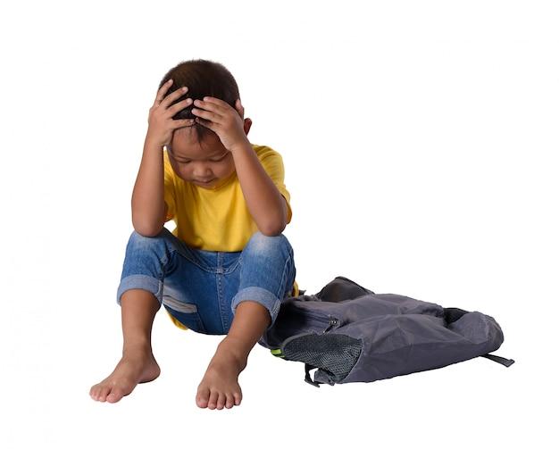 Pequeño muchacho asiático triste que se sienta en piso con la mochila aislada en el fondo blanco
