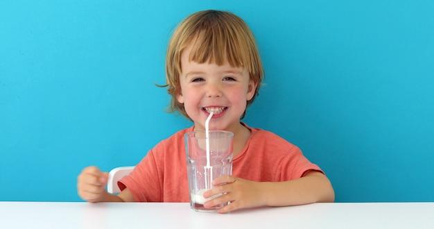 El pequeño muchacho lindo está bebiendo la leche