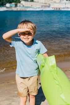Pequeño muchacho lindo que sonríe en la playa