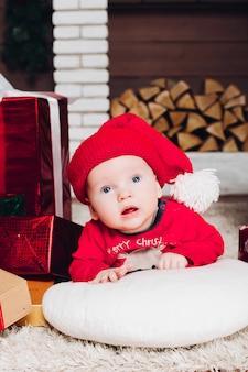 Pequeño muchacho de papá noel que miente en piso en casa adornada con los regalos de navidad