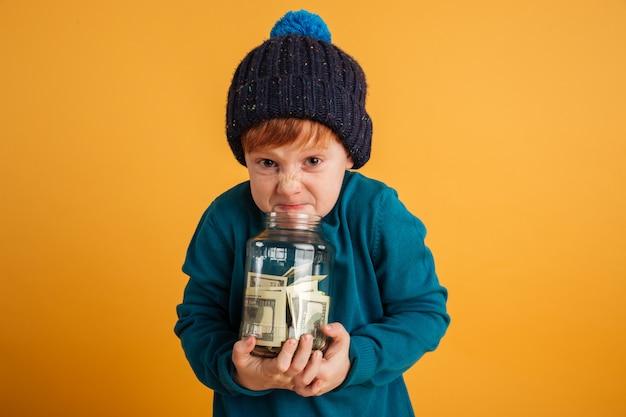 Pequeño muchacho pelirrojo enojado enojado que sostiene el tarro con el dinero.