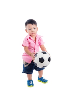 Pequeño muchacho preescolar asiático que sostiene la bola sobre el fondo blanco